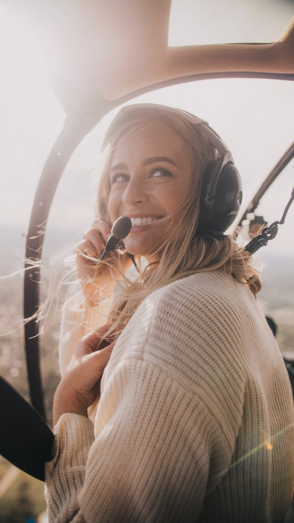 woman in a white knit sweater inside a helicopter