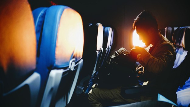 Mann im Flugzeug mit Aktentasche